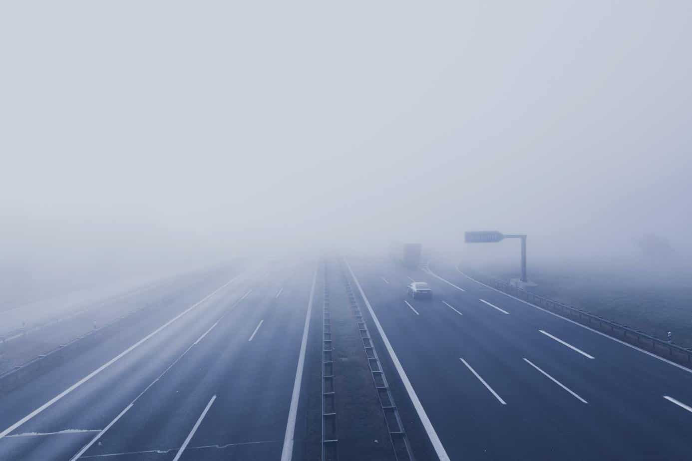 avoid highway hypnosis - truck entering the fog of an empty highway