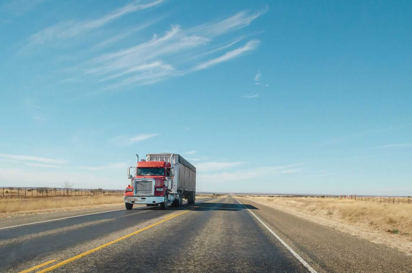 how much truck drivers make - red truck approaching on two lane highway